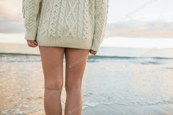 Mid section of a young woman in sweater standing on the beach