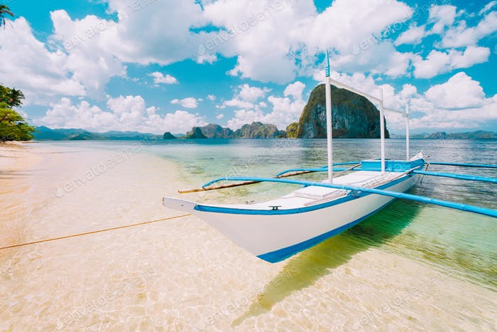 White banca island hopping boat at Las cabanas beach with amazing Pinagbuyutan island in background