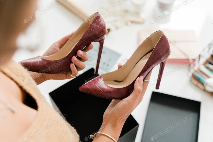 Pair of fashionable leather high-heeled shoes held by young female shopper