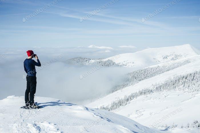 Hombre bebiendo de copa en la cima de las montañas de los Cárpatos