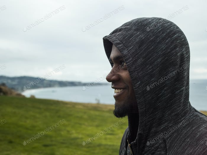 Close up of a smiling young men wearing a hoodie.