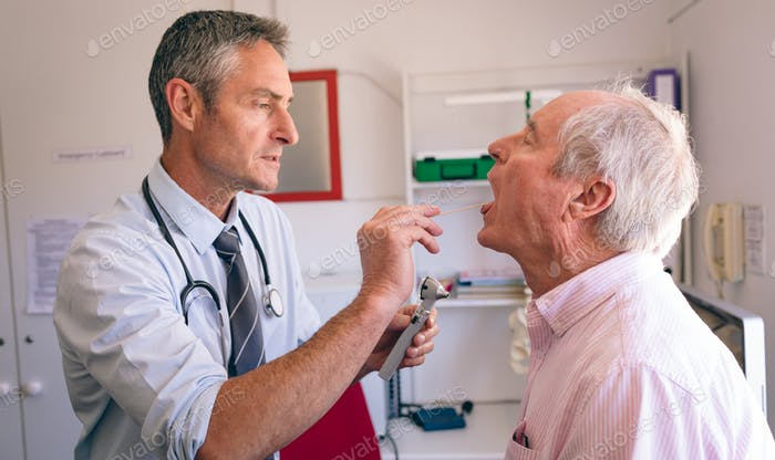 Male doctor checking senior male patient mouth with otoscope at clinic at retirement home