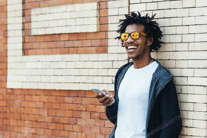 Afro young man using mobile phone bicycle.