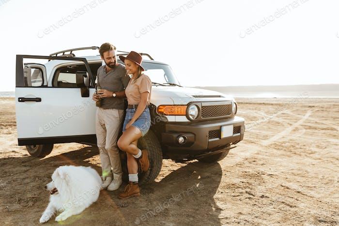 Loving couple with dog samoyed outdoors near car.