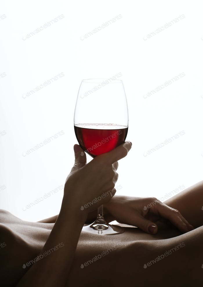 Middle aged caucasian lying back female model holds wineglass on her stomach