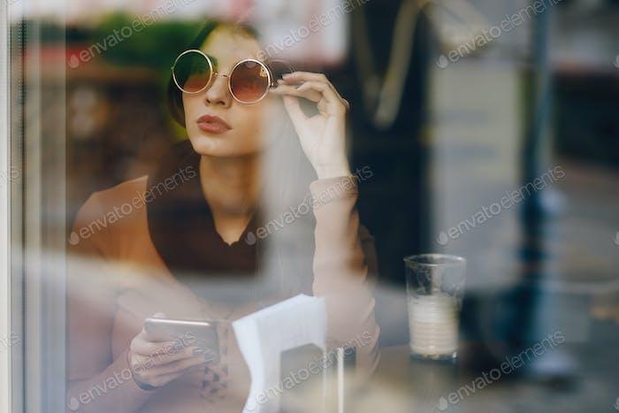 Thumbnail for Brünette Mädchen mit Telefon während bei ein restaurant