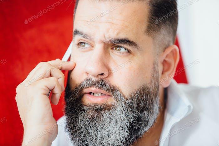 Close-up of bearded man phoning