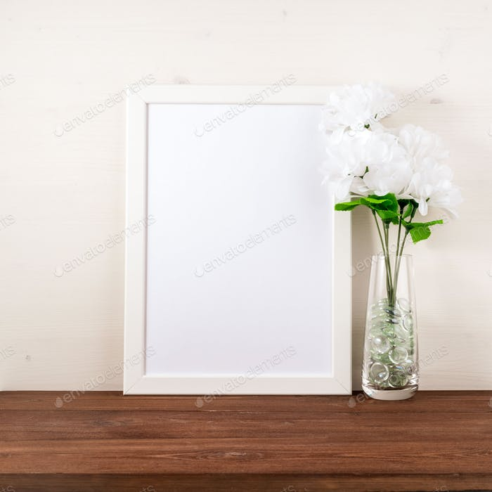 White frame, flower in glass bottle on dark brown wooden table a