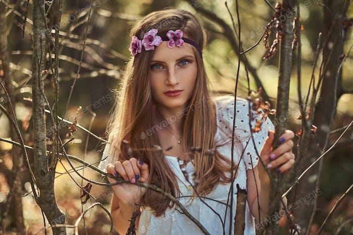 Schöne Frau in einem weißen Kleid und lila Kranz auf Kopf posiert in einem grünen Herbstwald.
