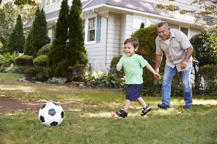Großvater spielen Fußball in Garten mit Enkel