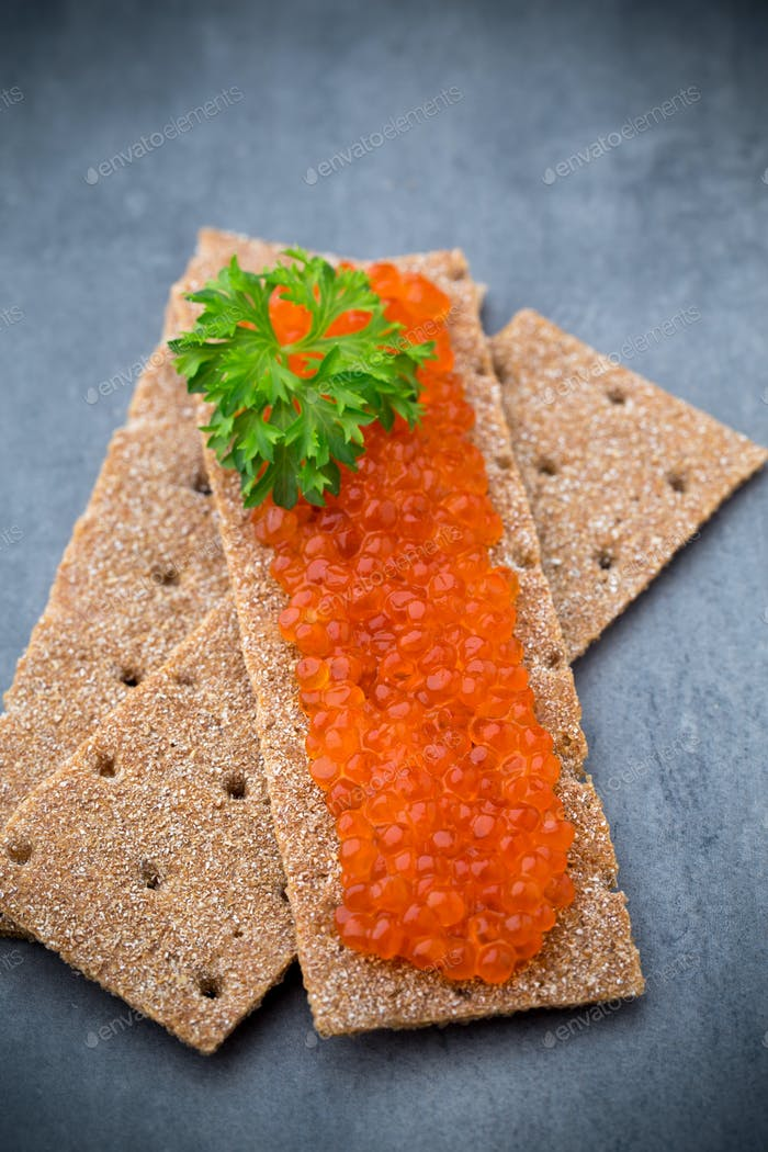 Crispbread with soft cheese with herbs and salmon roe.