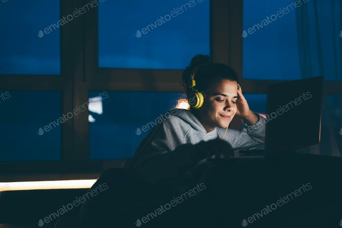 Woman using laptop and internet connection by night at home on the sofa.