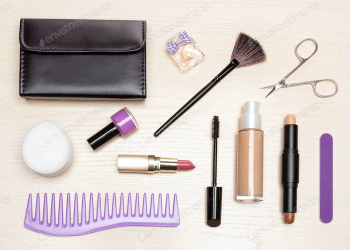 Basic contents of women cosmetic bag on wooden table, flat lay