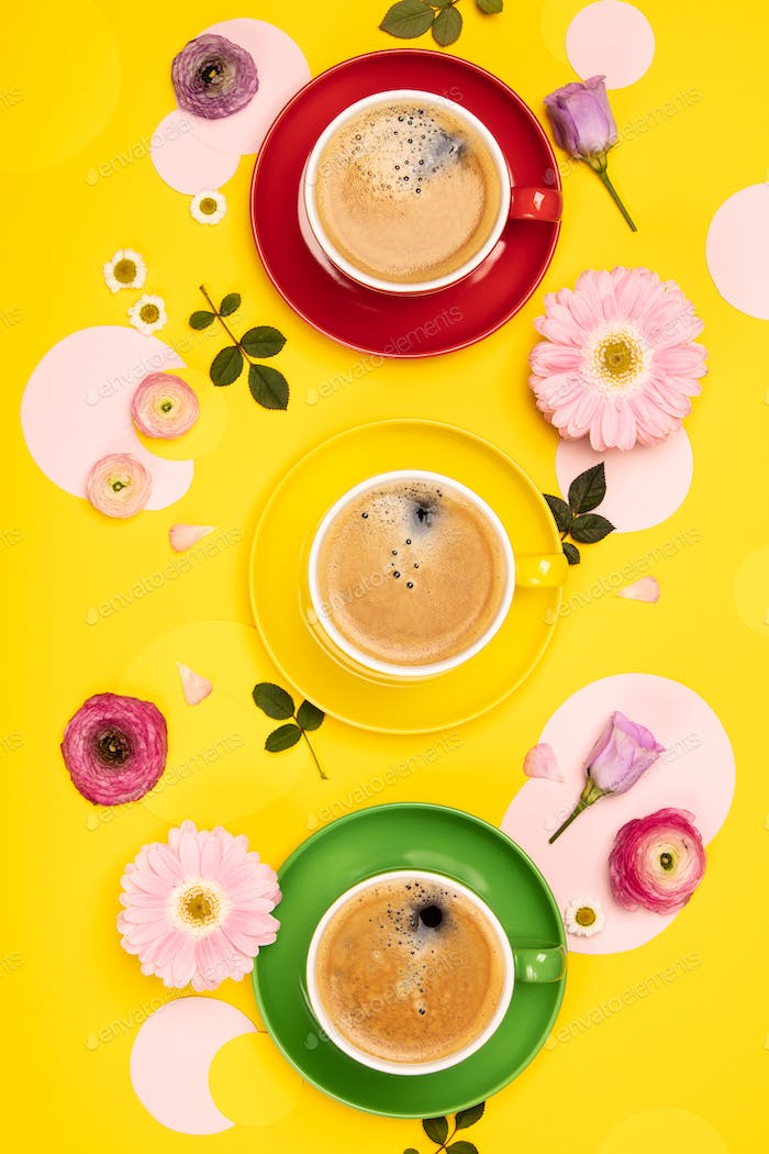 Cups of Coffee and colorful paper circles on yellow paper background