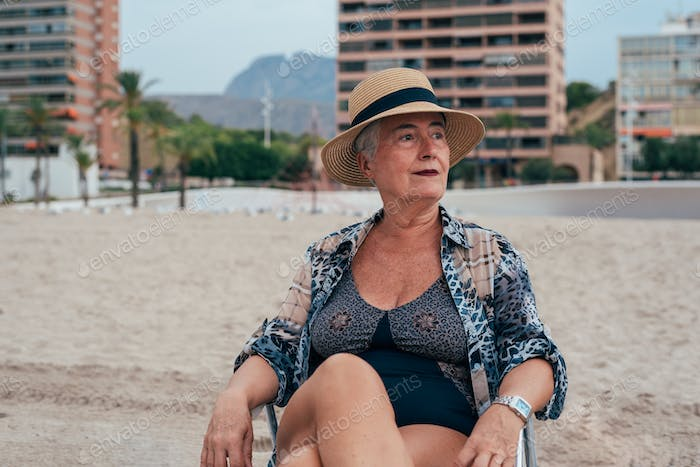 Elderly woman on the beach wearing a straw hat