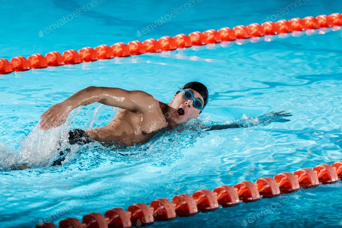 drops of water near swimmer with opened mouth training in swimming pool