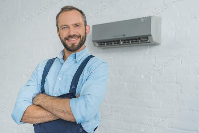 smiling bearded repairman posing with crossed arms, with air conditioner on wall