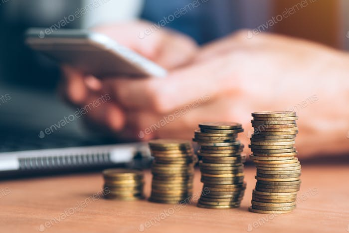 Geschäftsmann mit Smartphone mit gestapelten Münzen im Vordergrund