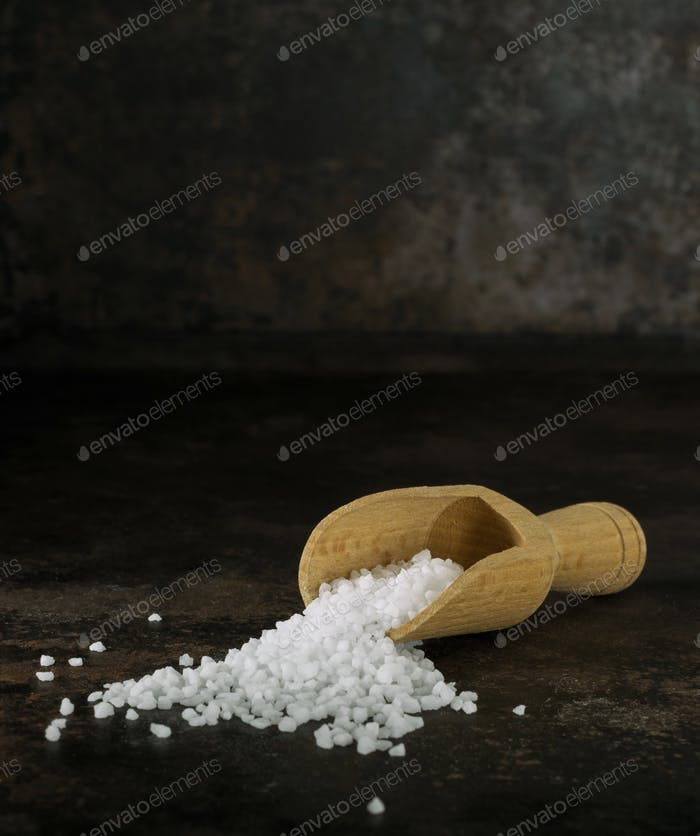 A wooden scoop of salt crystals
