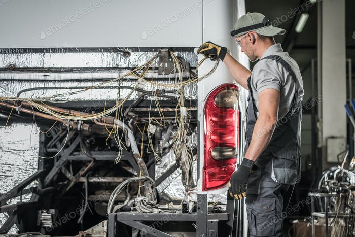 Bus Service Technician Staying in Front of Vehicle With No Diesel Engine Inside