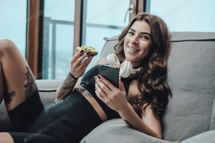 Seductive woman in sportswear with headphones and telephone