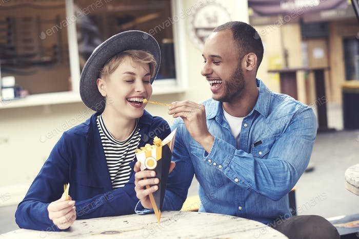 Smiley couple sharing fast food