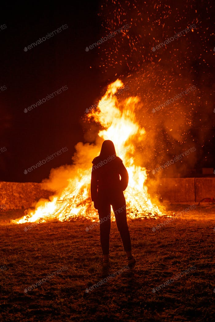 Silhouette of a woman contemplating a giant bonfire