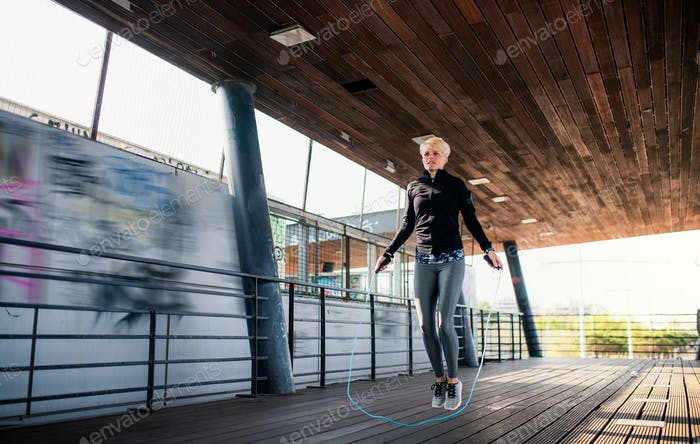 A young sportswoman doing exercise outdoors, skipping