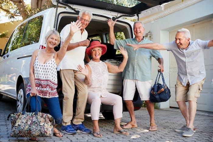 Vertical de emocionado Amigos mayores carga equipaje en el maletero de coche a punto de salir para vacaciones