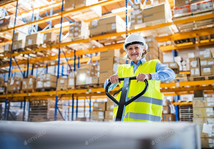 A senior woman warehouse worker pulling a pallet truck with boxes.