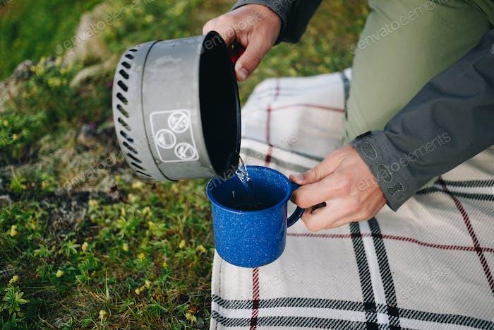 Mann gießt Wasser aus Gas-Campingkocher