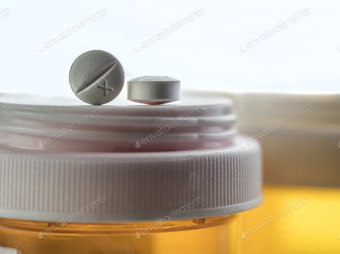 Two pills white on a bottle of medicines, conceptual image