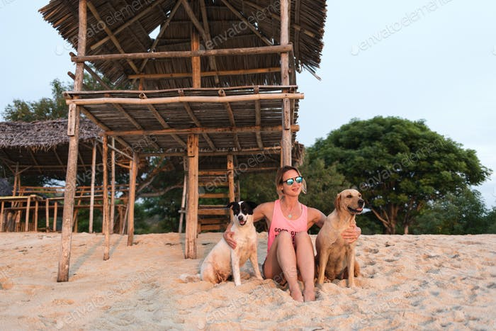 young woman or girl relaxing with two pets, dogs on sunny sandy beach