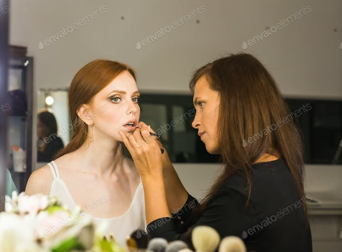 Make-up artist in the studio doing makeup beauty girl