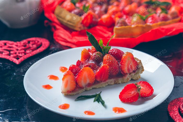 Strawberry pie on white plate black wooden table. One piece.  Romantic. Love. Heart. Toned phot