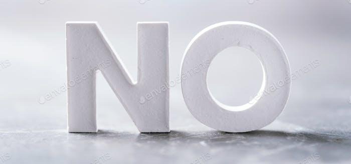 Wort NEIN gemacht mit Zementbuchstaben auf grauem Marmorhintergrund. Kopiere Leerzeichen. Business-Konzept
