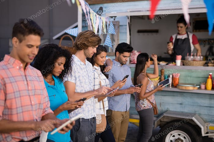Friends interacting while using mobile phone and digital tablet at counter