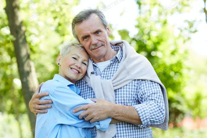 Glückliche Seniorenpaar umarmen in Park