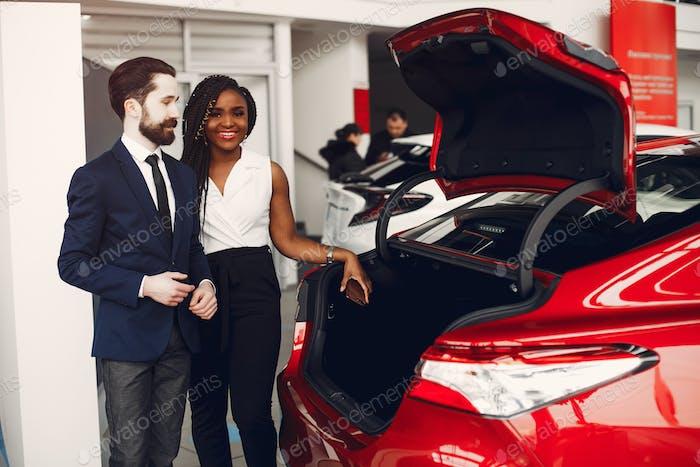 Stylish black woman in a car salon