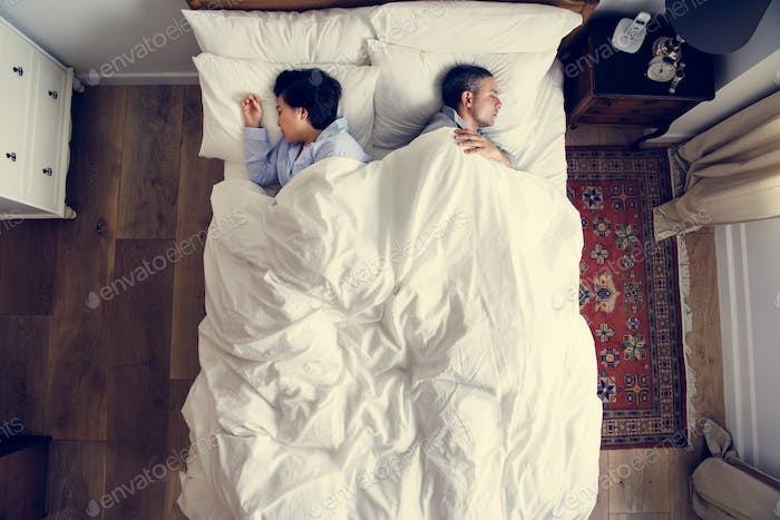 Interracial couple sleeping back to back on the bed