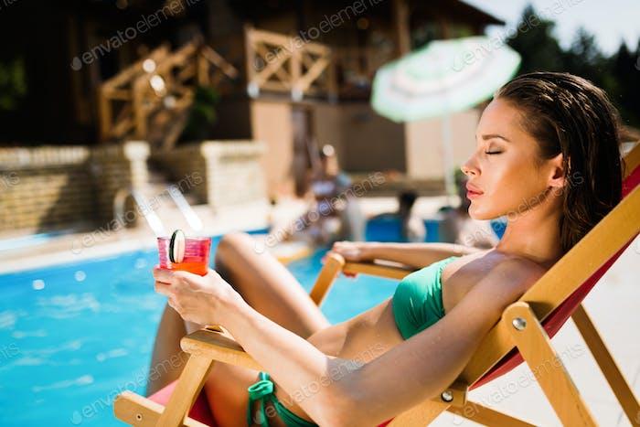 Beautiful woman enjoying her drink at poolside