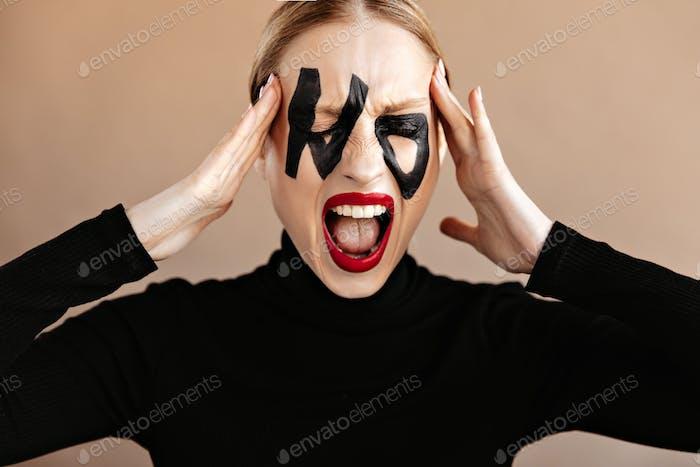 Mujer con labios rojos vestidos con top negro grita y toca la cabeza está alarmada. Retrato de chica con