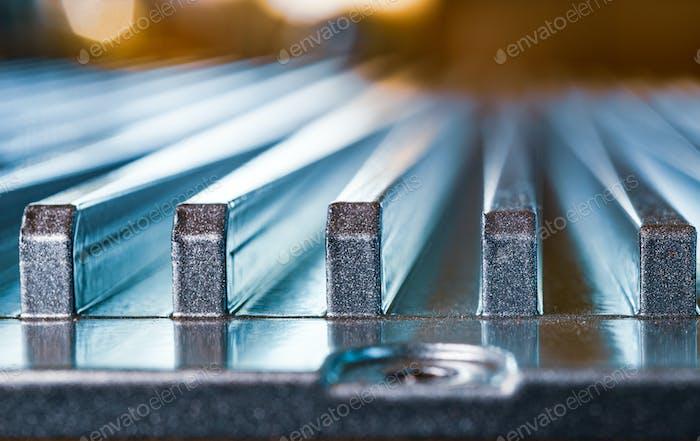 Geriffelte Metalloberfläche mit Schraubenloch