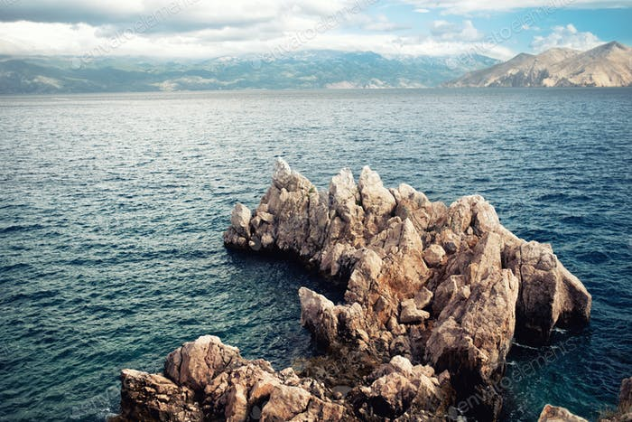 Island cliffs and seascape, aerial view with calm sea and clear sky. Soft, vintage effect on photo