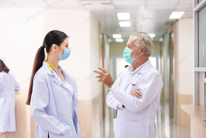 senior doctor talking with female doctor at hospital