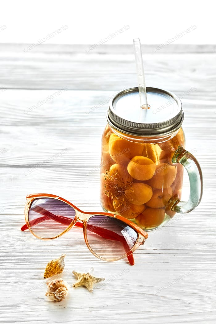 yellow cocktail juice with apricot,  sunglasses and shells