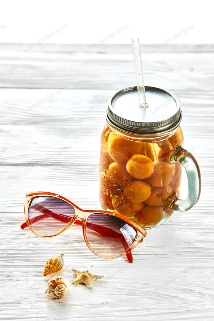 gelber Cocktailsaft mit Aprikose, Sonnenbrillen und Muscheln