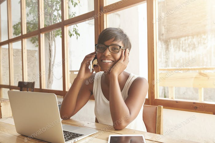 Attractive young woman discussing her business projects on phone. Smiling brunette with olive skin a