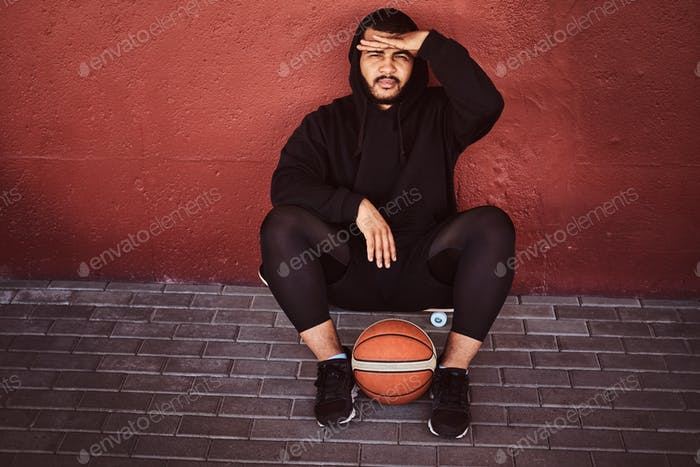 African-American bearded guy sitting on a skateboard with basketball and leaning on a wall.