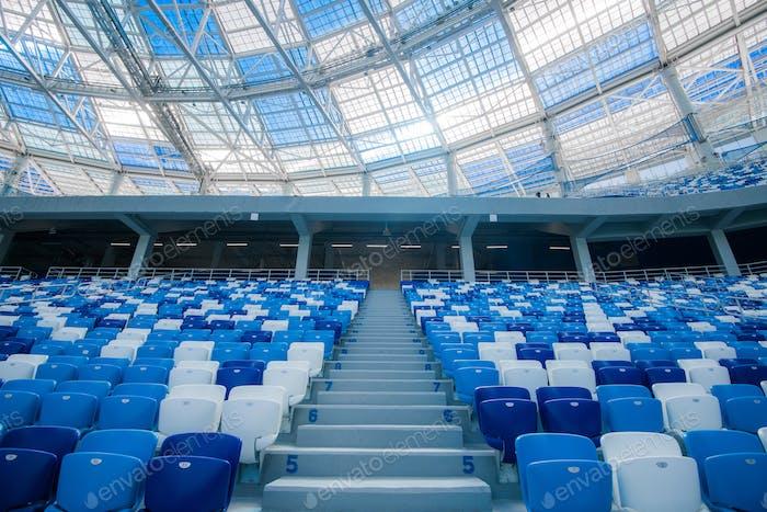 Escaleras de cemento y asientos azules dentro del estadio de fútbol